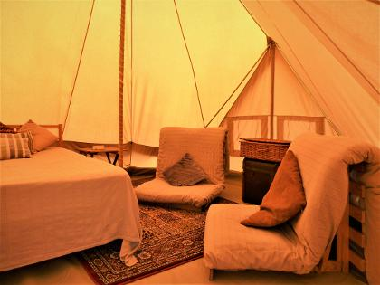Inside our Family Bell tent - the interior view of our family glamping holiday Bell tents, with a double bed, four futon sofabed and solar power! Off-grid solar powered glamping holidays at Woodland Escape in the heart of rural Somerset