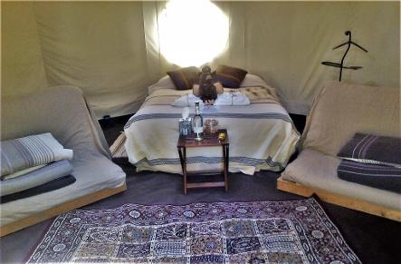 Inside a luxury off-grid Stargazer Yurts complete with double bed, rugs, single futon sofabeds. coat stand, table, bottled water and other luxury furnishings and decor at Woodland Escape - wegh.co.uk - woodlandescape.co.uk
